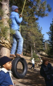 Student standing on tire swing.