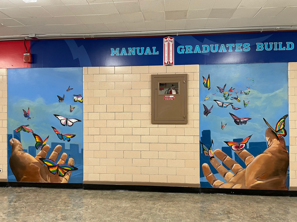 Wide shot of the two sections of the mural on the wall at McAuliffe/Manual. Shows brown-skinned hands opening to a blue sky, with many butterflies flying into the sky in the colors of the LGBTQ+ pride flags.